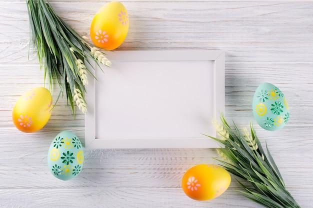 Pascua simulacro con marco de fotos. coloridos huevos de pascua y conejito de madera decorativa. celebración, concepto de vacaciones. plano, vista superior, espacio de copia