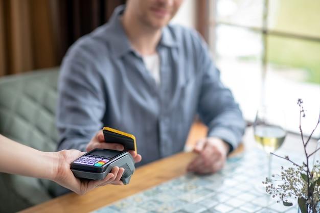 Pase de pago. hombre de camisa gris con smartphone sentado en la mesa haciendo pago con cheque en el restaurante por la tarde, la cara no es visible