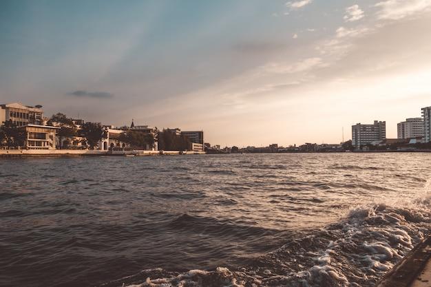 Pasee en bote por el río chao phraya por la noche y vea el asentamiento local a lo largo de la orilla.