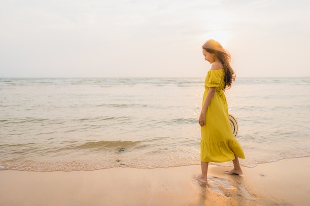 El paseo asiático joven hermoso de la mujer del retrato en la playa y el océano del mar con sonrisa feliz se relajan