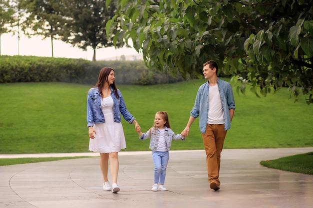 Paseo familiar feliz en el parque en verano