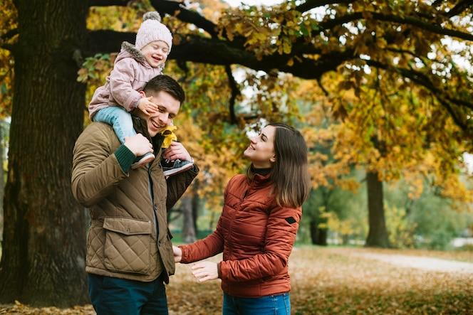 Paseo familiar joven en el parque de otoño