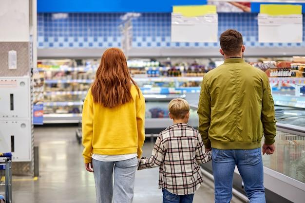 Paseo familiar en el supermercado, padres caucásicos tomados de la mano de su hijo, disfrutan de las compras. vista desde atrás, vista trasera