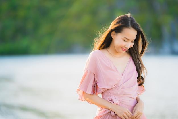 Paseo feliz de la sonrisa asiática joven hermosa de la mujer del retrato en el mar al aire libre tropical de la playa de la naturaleza