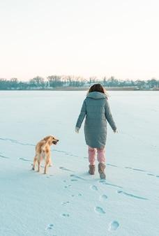 Paseo invernal de joven hermosa mujer morena con ropa de abrigo en la nieve con perro. concepto de invierno nevando.