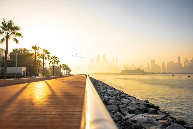 Paseo marítimo en la mañana del puerto deportivo de dubai al amanecer.