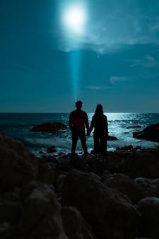 Paseo marítimo nocturno y pareja tomados de la mano