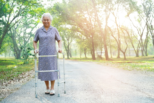 Paseo mayor asiático o mayor de la mujer mayor de la mujer mayor con el caminante en parque.
