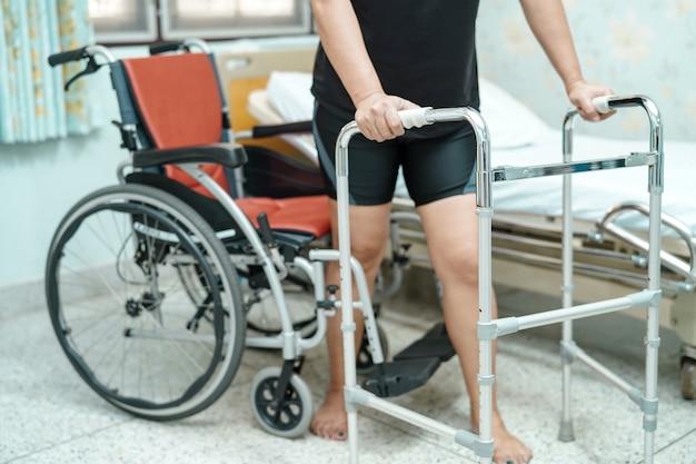 Paseo paciente asiático de la mujer de mediana edad de la señora con el caminante en la sala de hospital de enfermería