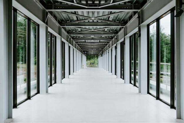 Pasillo blanco con puertas de vidrio y techo de metal en un edificio moderno.