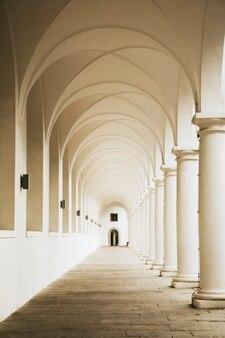 Pasillo clásico con columnas blancas.