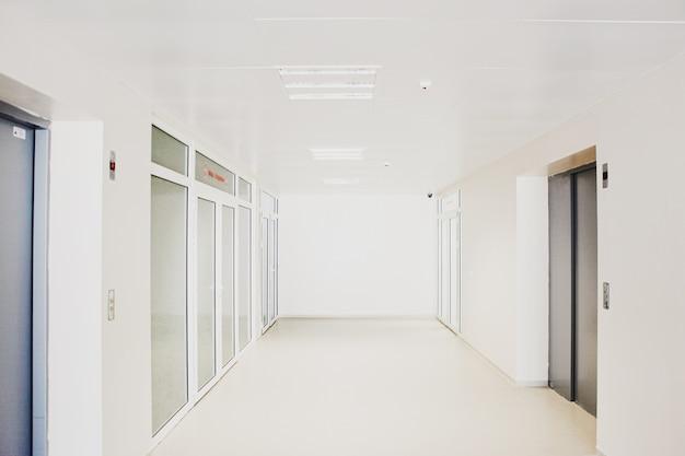 Pasillo de hospital vacío con puertas de vidrio