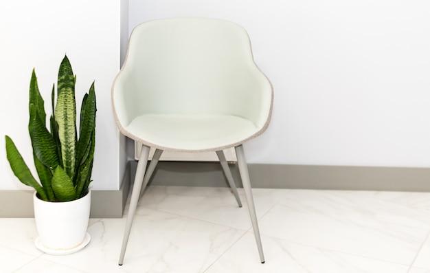 Pasillo con silla para pacientes en un hospital moderno.