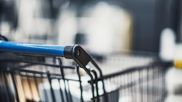 Pasillo del supermercado con carrito de compras en grandes almacenes borrosos