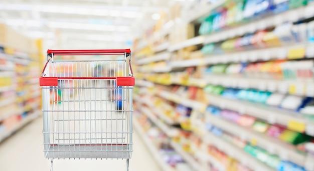 Pasillo de supermercado con carrito de compras rojo vacío