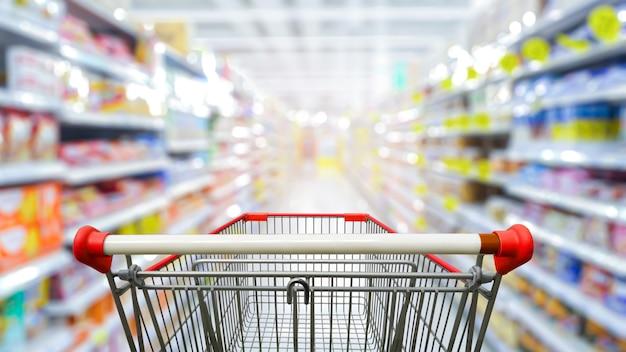Pasillo del supermercado con carrito de compras rojo vacío.