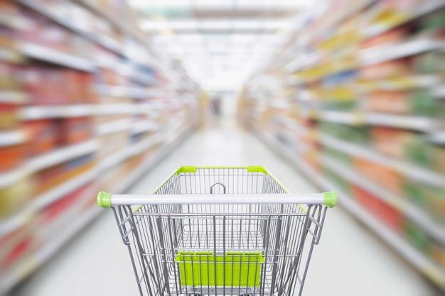 Pasillo de supermercado con carrito de compras verde vacío en movimiento
