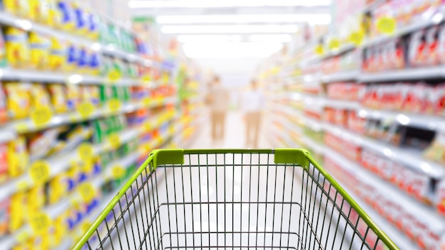 Pasillo del supermercado con carrito de compras verde vacío.