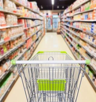 Pasillo de supermercado con concepto de negocio de carrito de compras vacío