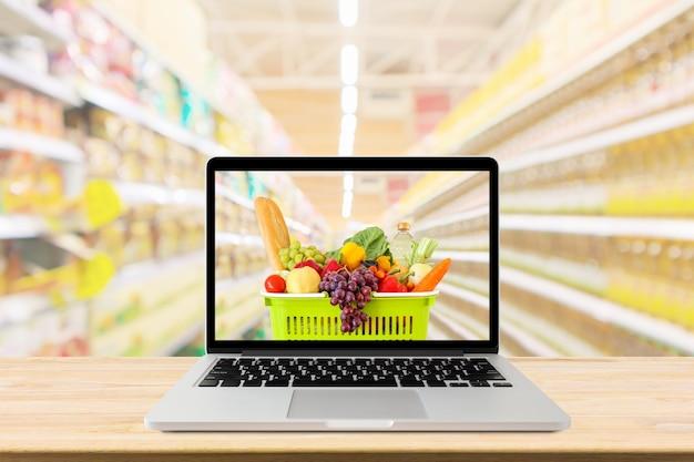 Pasillo de supermercado fondo borroso con computadora portátil y carrito de compras en el concepto de línea de comestibles de mesa de madera