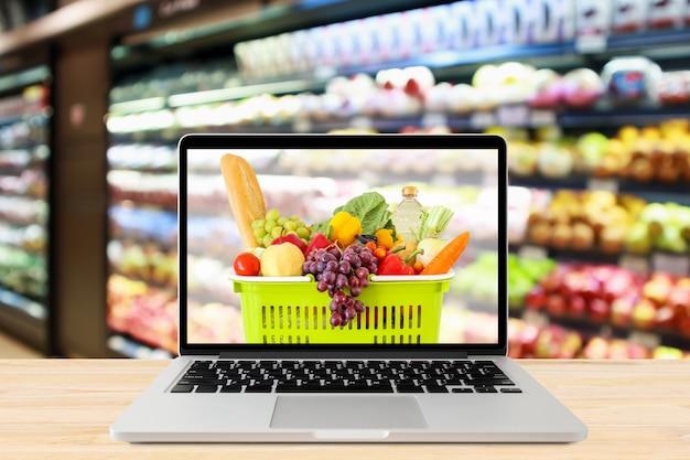 Pasillo del supermercado fondo borroso con ordenador portátil y cesta de la compra en la mesa de madera concepto online de abarrotes
