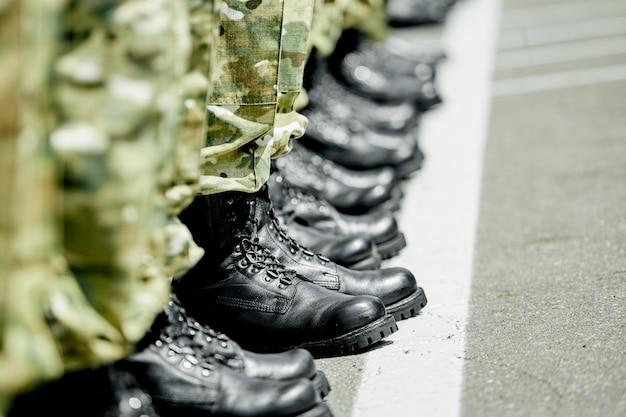 Un paso adelante, botas militares del ejército en fila