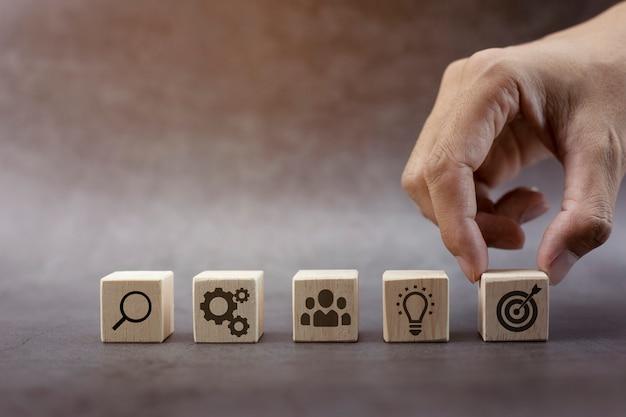 Paso de bloque de madera de pila de mano en la mesa con estrategia comercial de icono y plan de acción