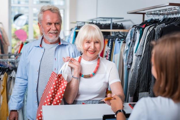 Paso de compra final. familia de ancianos positiva pasando una tarjeta de crédito a la vendedora mientras está satisfecho con sus compras en la tienda de compras