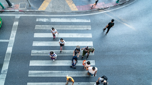 Paso de peatones de vista aérea superior con personas que cruzan la carretera con señalización. concepto peatones pasando por un paso de peatones. hora punta en la ciudad