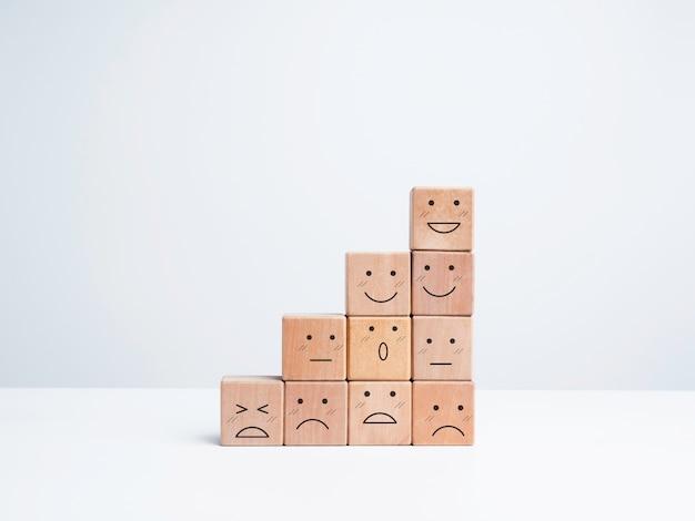 Los pasos de crecimiento empresarial con emociones felices y tristes en caras de emoticonos se organizan en bloques de madera aislados sobre fondo blanco, estilo minimalista. satisfacción, evaluación, concepto de encuesta de calificación.