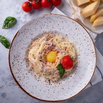 Pasta alla carbonara tocino, huevo, queso parmesano y salsa de crema. vista superior. de cerca