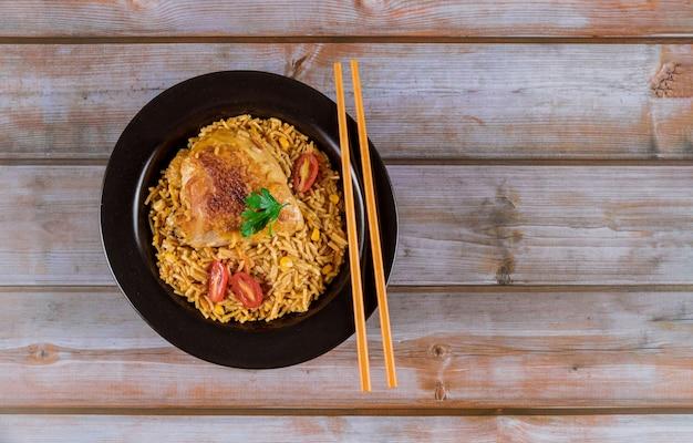 Pasta y arroz con pollo y verduras en un tazón negro.