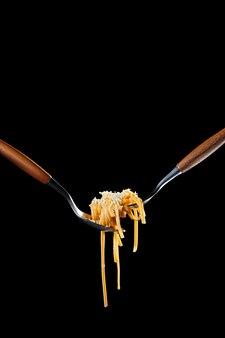 Pasta bigoli cocida retorcida en tenedor con aceite de oliva y parmesano