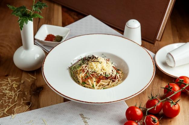 Pasta boloñesa con queso tomate sal y pimienta en la mesa