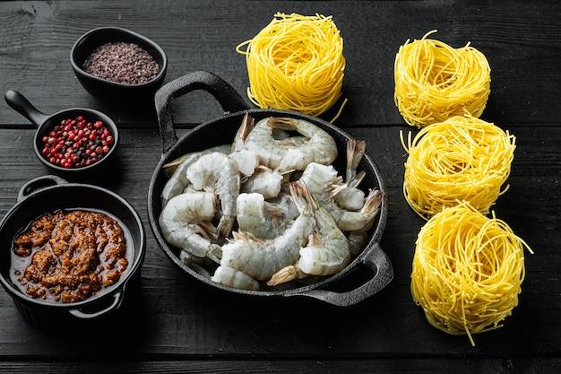 Pasta con camarones, tomate y salsa pesto ingredientes, sobre mesa de madera negra