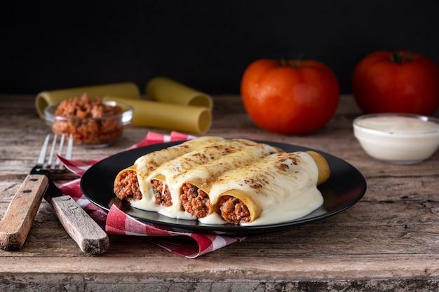 Pasta de canelones de carne deliciosa sobre mesa de madera rústica