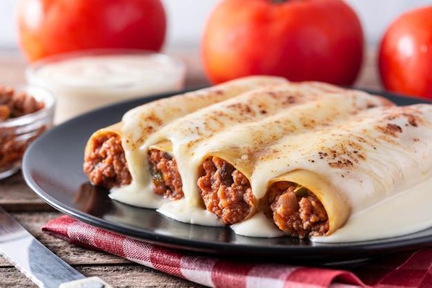 Pasta de canelones de carne deliciosa sobre mesa de madera