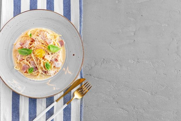 Pasta carbonara con tocino y crema servida en un plato de cerca
