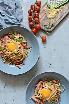Pasta carbonara con tocino y parmesano en placas grises sobre la mesa, restaurante sirven
