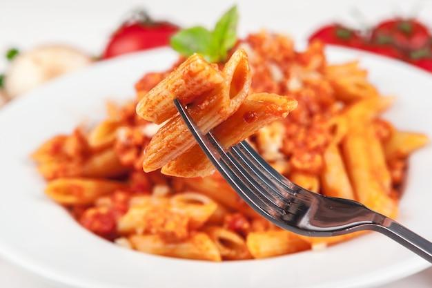 Pasta con carne, salsa de tomate y verduras sobre la mesa