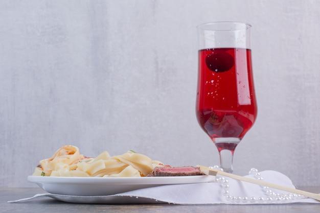 Pasta con carne y vaso de limonada roja sobre placa blanca.