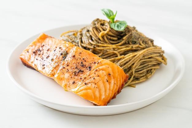 Pasta casera con espaguetis al pesto con salmón a la parrilla - estilo de comida italiana