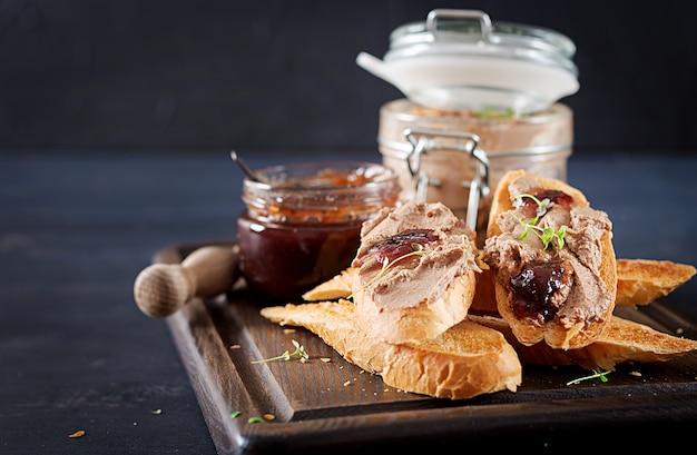 Pasta casera de hígado de pollo o paté en frasco de vidrio con tostadas y mermelada de arándanos rojos con chile.