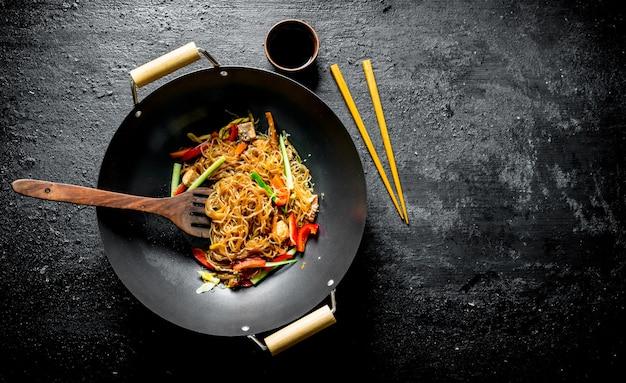 Pasta de celofán chino en una sartén wok con espátula y palillos. sobre fondo rústico negro