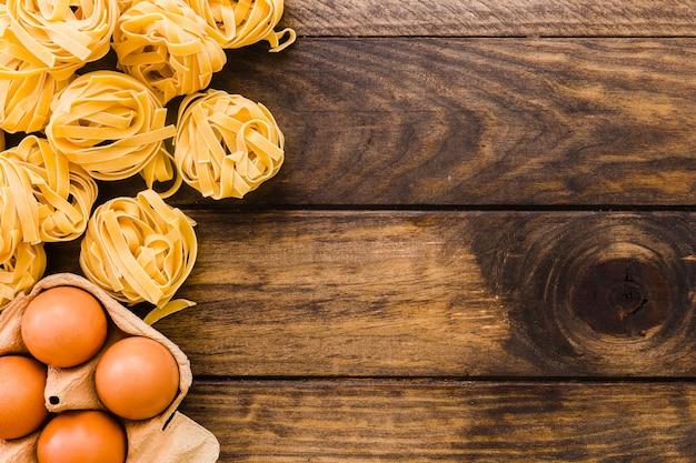 Pasta cerca de cartón de huevos