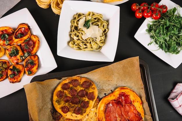 Pasta cerca de pizzas y romero