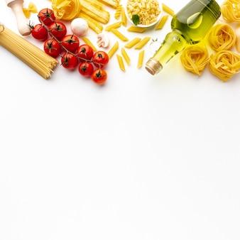 Pasta sin cocer de alto ángulo con tomates aceite de oliva y espacio de copia