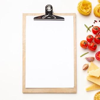 Pasta sin cocer e ingredientes con maqueta de portapapeles