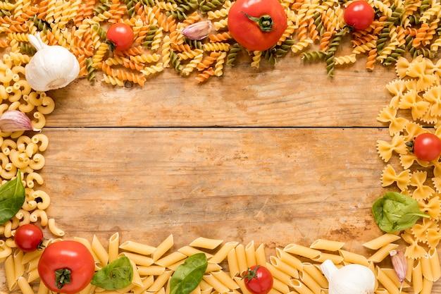 Pasta sin cocer con tomate; hojas de ajo y albahaca dispuestas sobre una superficie texturizada.