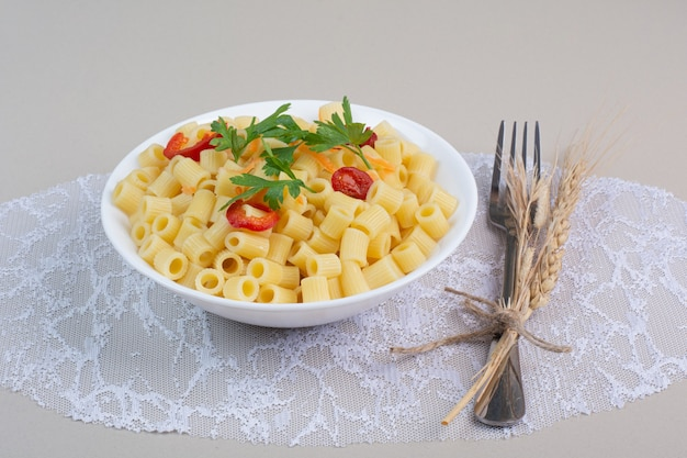 Pasta cocida con perejil y rodajas de tomate en un tazón blanco